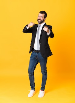 Full-length shot of business man over isolated yellow points finger at you while smiling