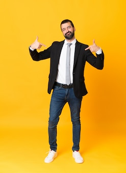 Full-length shot of business man over isolated yellow  proud and self-satisfied