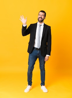 Full-length shot of business man over isolated yellow saluting with hand with happy expression