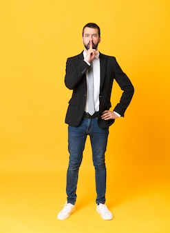 Full-length shot of business man over isolated yellow showing a sign of silence gesture putting finger in mouth