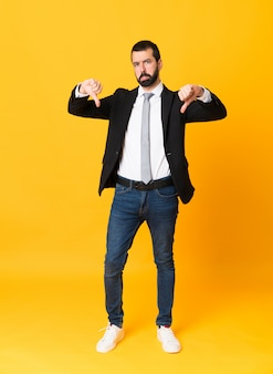 Full-length shot of business man over isolated yellow showing thumb down