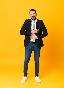 Full-length shot of business man over isolated yellow  smiling a lot