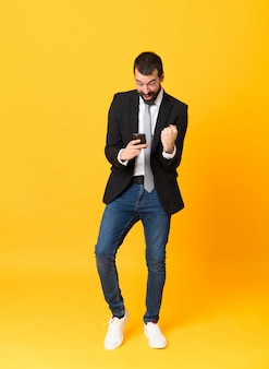 Full-length shot of business man over isolated yellow surprised and sending a message