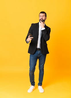 Full-length shot of business man over isolated yellow thinking and sending a message Premium Photo