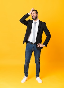 Full-length shot of business man over isolated yellow wall has realized something and intending the solution