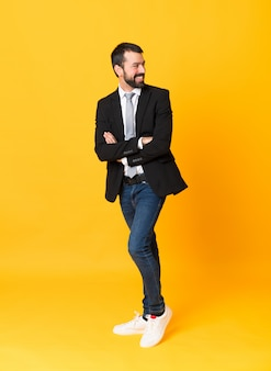 Full-length shot of business man over isolated yellow with arms crossed and happy
