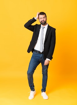 Full-length shot of business man over isolated yellow with an expression of frustration and not understanding