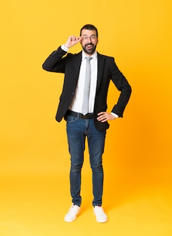 Full-length shot of business man over isolated yellow  with glasses and surprised