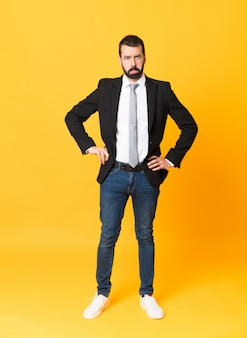 Full-length shot of business man over isolated yellow with sad and depressed expression
