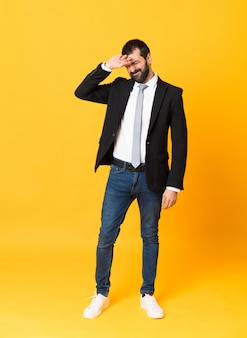Full-length shot of business man over isolated yellow with tired and sick expression