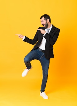 Full-length shot of business man pointing to the lateral over isolated yellow