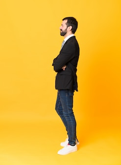 Full-length shot of business man over yellow in lateral position