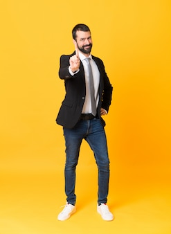 Full-length shot of business man over yellow showing and lifting a finger