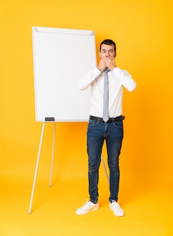 Full-length shot of businessman giving a presentation on white board covering mouth with hands