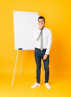 Full-length shot of businessman giving a presentation on white board over isolated yellow background covering mouth with hands