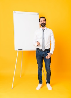 Full-length shot of businessman giving a presentation on white board over isolated yellow background laughing