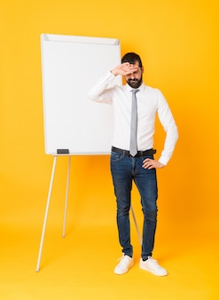 Full-length shot of businessman giving a presentation on white board over isolated yellow background with tired and sick expression