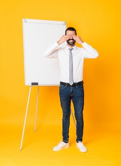 Full-length shot of businessman giving a presentation on white board over isolated yellow covering eyes by hands