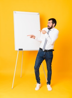 Full-length shot of businessman giving a presentation on white board over isolated yellow frightened and pointing to the side