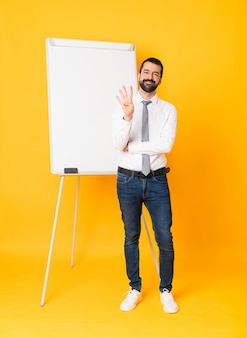 Full-length shot of businessman giving a presentation on white board over isolated yellow happy and counting four with fingers