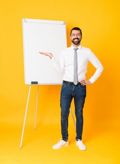 Full-length shot of businessman giving a presentation on white board over isolated yellow holding copyspace imaginary on the palm