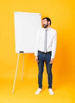 Full-length shot of businessman giving a presentation on white board over isolated yellow making doubts gesture looking side
