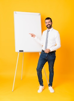 Full-length shot of businessman giving a presentation on white board over isolated yellow pointing finger to the side