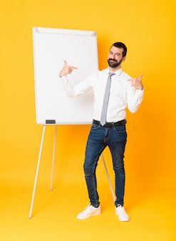 Full-length shot of businessman giving a presentation on white board over isolated yellow  proud and self-satisfied
