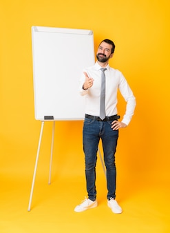 Full-length shot of businessman giving a presentation on white board over isolated yellow shaking hands for closing a good deal