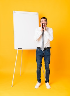 Full-length shot of businessman giving a presentation on white board over isolated yellow shouting and announcing something