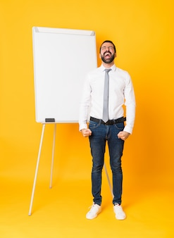Full-length shot of businessman giving a presentation on white board over isolated yellow shouting to the front with mouth wide open