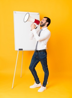 Full-length shot of businessman giving a presentation on white board over isolated yellow shouting through a megaphone