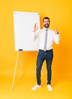 Full-length shot of businessman giving a presentation on white board over isolated yellow showing ok sign and thumb up gesture