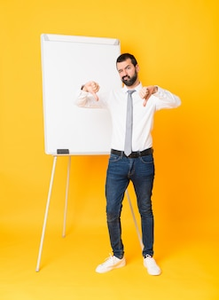 Full-length shot of businessman giving a presentation on white board over isolated yellow showing thumb down