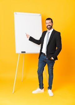 Full-length shot of businessman giving a presentation on white board over isolated yellow