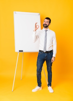Full-length shot of businessman giving a presentation on white board over yellow showing ok sign with fingers