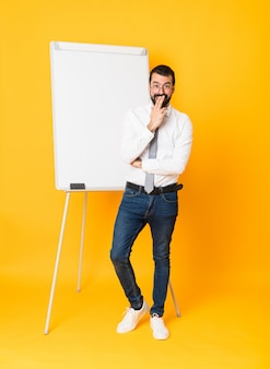 Full-length shot of businessman giving a presentation on white board over yellow with glasses and surprised