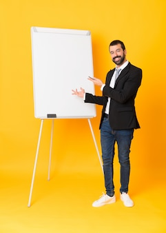 Full-length shot of businessman giving a presentation on white board
