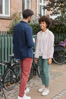 Full length shot of cheerful woman and man meet together on street near house, stand opposite each other