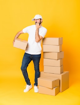Full-length shot of delivery man among boxes over isolated yellow background nervous and scared putting hands to mouth