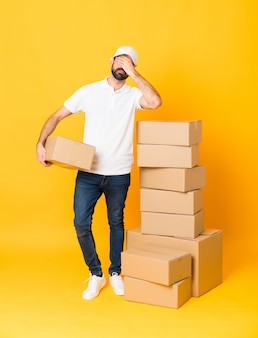 Full-length shot of delivery man among boxes over isolated yellow covering eyes by hands.