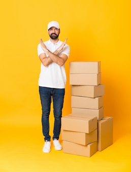 Full-length shot of delivery man among boxes over isolated yellow making no gesture