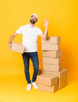 Full-length shot of delivery man among boxes over isolated yellow saluting with hand with happy expression