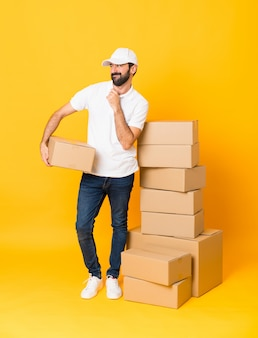 Full-length shot of delivery man among boxes over isolated yellow  scheming something