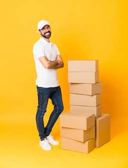 Full-length shot of delivery man among boxes over isolated yellow with glasses and smiling