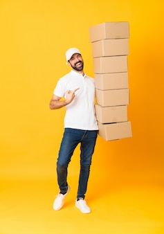 Full-length shot of delivery man among boxes over isolated yellow
