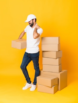 Full-length shot of delivery man among boxes suffering from pain in shoulder for having made an effort