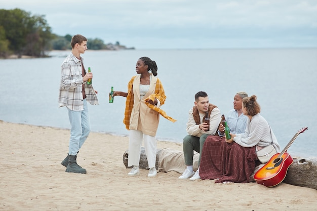 Full length shot of diverse group of friends camping on beach in autumn and having fun together outdoors