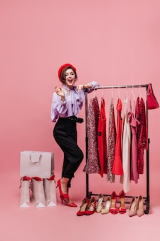 Full-length shot of elegant lady in red hat and black-and-purple outfit posing with hanger with elegant dresses, shoes and packages.