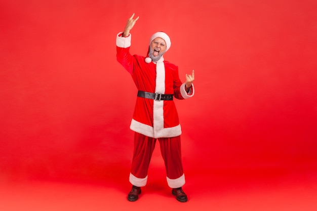 Full length shot of excited elderly man with gray beard wearing santa claus costume showing rock and roll sing to camera and screaming with crazy look. indoor studio shot isolated on red background.